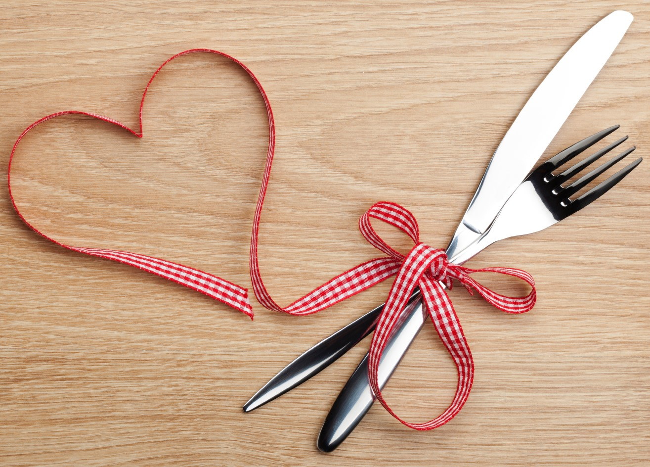 Valentine's Day heart shaped red ribbon and silverware. On wooden table background