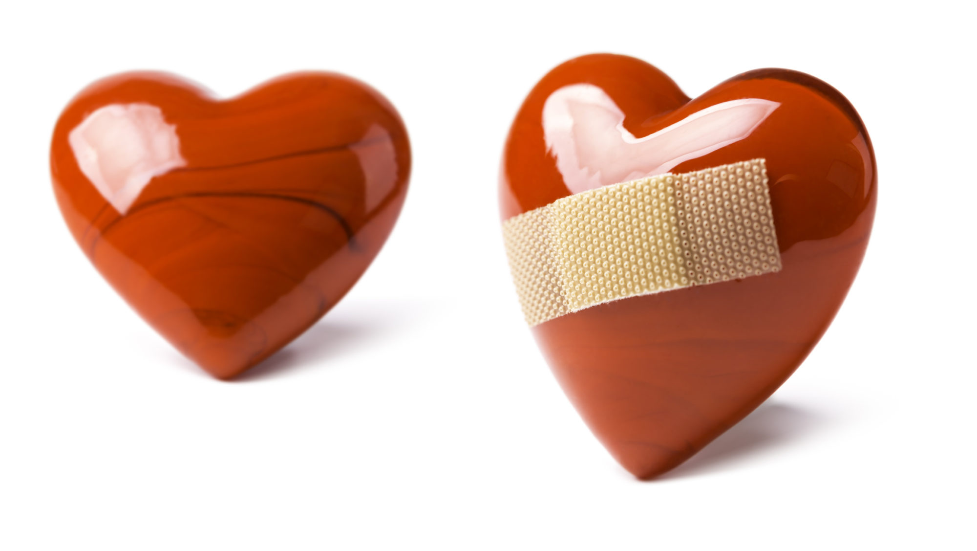 red, ceramic hearts with a bandage on white background